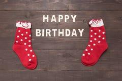 El feliz cumpleaños y los calcetines están en fondo de madera Foto de archivo