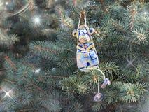El feliz mono de la cerámica de la arcilla se sienta en el árbol entre las estrellas Foto de archivo