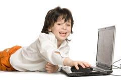 El feliz muchacho con la computadora portátil imágenes de archivo libres de regalías
