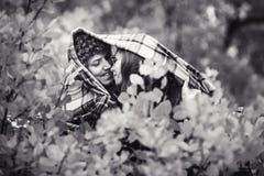 El feliz par feliz está ocultando detrás de día del otoño de la tela escocesa fotografía de archivo libre de regalías