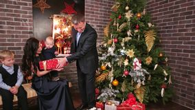 El ` feliz s Eve, marido del Año Nuevo de la familia da los regalos a su esposa y niños, fiesta de Navidad en la familia, padre almacen de metraje de vídeo