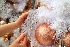 El ` femenino s da el adornamiento del árbol de navidad con un ornamento formado copo de nieve del brillo Imágenes de archivo libres de regalías