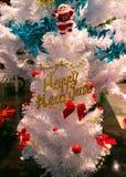 El ` femenino s da el adornamiento del árbol de navidad con un ornamento formado copo de nieve del brillo Foto de archivo libre de regalías