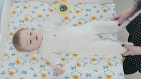 El ` femenino s da a tactos el pequeño bebé en panal metrajes