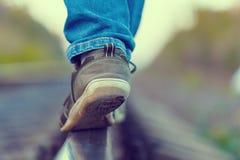 El ferrocarril cerca las zapatillas de deporte de los pies con barandilla Fotografía de archivo libre de regalías