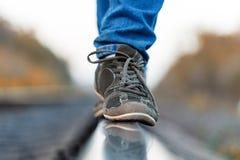 El ferrocarril cerca las zapatillas de deporte de los pies con barandilla Imagen de archivo