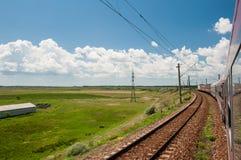 El ferrocarril y el tren van al horizonte en paisaje verde debajo del cielo azul con las nubes blancas Imagenes de archivo