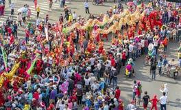 El festival de linterna chino con los dragones coloridos, león, banderas, coches, marchó en muchedumbre atraída las calles Fotos de archivo