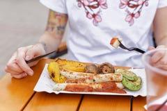 El festival local de la comida Una muchacha hermosa come las salchichas y las verduras fritas Imagen de archivo
