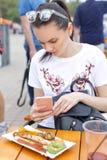 El festival local de la comida Una muchacha hermosa come las salchichas y las verduras fritas Fotos de archivo libres de regalías