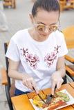 El festival local de la comida Una muchacha hermosa come las salchichas y las verduras fritas Imagenes de archivo