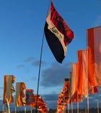 El festival señala agitar por medio de una bandera en crepúsculo contra el cielo dramático Fotografía de archivo