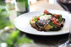 El filete asado a la parrilla del bistec de costilla con mantequilla de hierba y verduras asadas a la parrilla sirvi? en una plac imagen de archivo libre de regalías