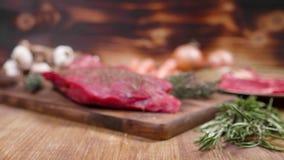 El filete crudo sazonó con la sal, la pimienta, el romero y el tomillo metrajes
