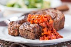 El filete de carne de vaca asado a la parrilla con la salsa de la salsa secó los tomates, pimientas rojas Foto de archivo