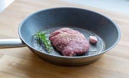 El filete de carne de vaca se fríe en una cacerola con romero y ajo Imágenes de archivo libres de regalías