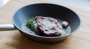 El filete de carne de vaca se fríe en una cacerola con romero y ajo Fotografía de archivo libre de regalías