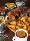 El filete de carne de vaca asado a la parrilla, las alas de pollo y el pollo empanado se pega con las patatas fritas y las salsas Imagen de archivo