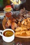 El filete de carne de vaca asado a la parrilla, las alas de pollo y el pollo empanado se pega con las patatas fritas y las salsas Fotos de archivo