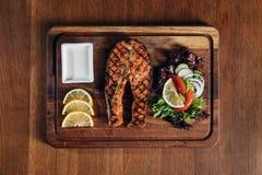 El filete de color salmón asado a la parrilla sirvió en el tablero de madera con el limón y la ensalada Imagen de archivo