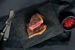 El filete de grupa de la carne de vaca as? raro Fondo negro, visi?n superior foto de archivo