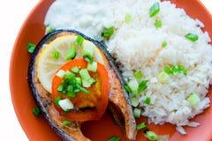 El filete del keta cocinó con el tomate, el arroz, la cebolla y el limón Foto de archivo