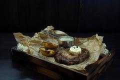 El filete jugoso asado a la parrilla con mantequilla y rebanadas de berenjena cocida en un tablero del vintage se opone en una ta fotografía de archivo libre de regalías