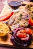 El filete jugoso del cerdo con una puntilla del tomillo fresco, limón y las verduras y salsa asadas a la parrilla sirvió en un ta imagenes de archivo