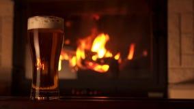 El filtrado tiró el vidrio lleno de cerveza refrescada apetitosa del refresco con la espuma rodeada por la chimenea almacen de video