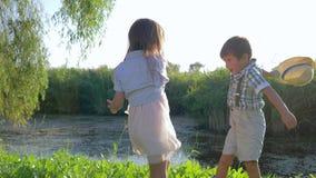 El fin de semana feliz, el muchacho y la muchacha se divierten con los sombreros de paja en manos cerca del lago al aire libre almacen de metraje de vídeo