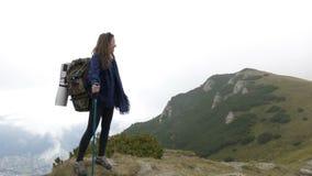 El final de la aventura de la mujer acertada del explorador que alcanza el top de la montaña que mira alrededor al paisaje asombr almacen de metraje de vídeo