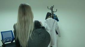 El final del día en la oficina Un trabajo de las hojas de la mujer joven El blonde hermoso viene a la suspensión y la saca metrajes
