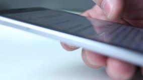 El finger de la mano funciona con la pantalla táctil del teléfono Noticias de la lectura, consiguiendo la información metrajes