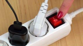 El finger de la mujer apaga el interruptor de la extensión de la electricidad con muchos enchufes metrajes