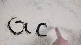 El finger escribe en un fondo de la harina blanca Visión superior 4K metrajes