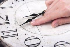 El finger femenino cambia el tiempo en un reloj imagen de archivo libre de regalías