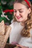 El firl rubio hermoso está abriendo un regalo del ` s del Año Nuevo en el backg Foto de archivo libre de regalías