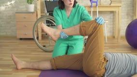 El fisioterapeuta ayuda a un hombre a hacer ejercicios de la recuperación cerca para arriba almacen de video