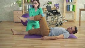 El fisioterapeuta ayuda a un hombre a hacer ejercicios de la recuperación metrajes