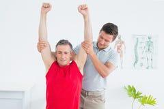 El fisioterapeuta de sexo masculino que estira un maduro sirve los brazos Fotos de archivo