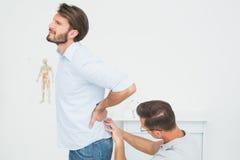 El fisioterapeuta de sexo masculino que examina sirve detrás imagen de archivo libre de regalías