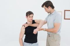 El fisioterapeuta de sexo masculino que examina un joven sirve el brazo imagen de archivo libre de regalías