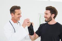 El fisioterapeuta de sexo masculino que examina un joven sirve la muñeca imagenes de archivo