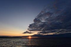 El flash del sol irradia en la puesta del sol de detrás las nubes Fotos de archivo