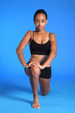 El flexor de la cadera del arrodillamiento estira por la mujer negra del ajuste Fotografía de archivo libre de regalías