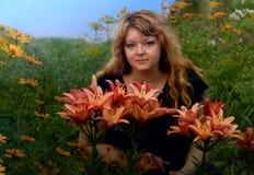 El florecimiento de la mujer joven vida-hermosa en el jardín se sienta entre las flores Imagen de archivo libre de regalías