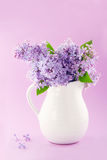 El florero blanco con un ramo de lila púrpura florece Imagen de archivo libre de regalías