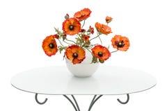 El florero con las amapolas rojas está en una mesa de centro, aislada en un blanco Fotos de archivo