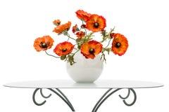 El florero con las amapolas rojas está en una mesa de centro, aislada en un blanco Fotografía de archivo libre de regalías