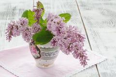 El florero con un ramo de primavera púrpura de la lila florece en te del vintage Foto de archivo libre de regalías